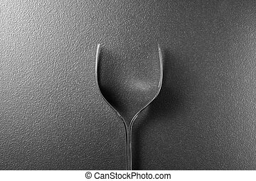 Wine glass made of forks on black background