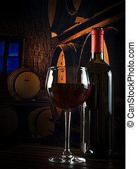 wine glass near bottle in old wine cellar
