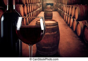 wine glass near bottle in old wine cellar with space for...