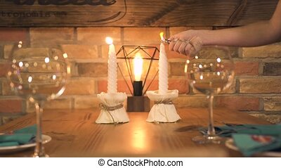 Wine glass standing on served dinner table with burning candle for romantic date in restaurant. Waitress lighting candle on evening table in r restaurant. Valentine day in romantic cafe.