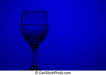 wine glass with water. blue monochrome background