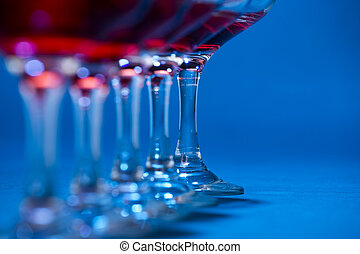 Detail of glasses filled with red wine over blue background.