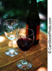 wine glasses and bottle set outside
