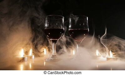 Wine glasses and burning candles in the smoke.
