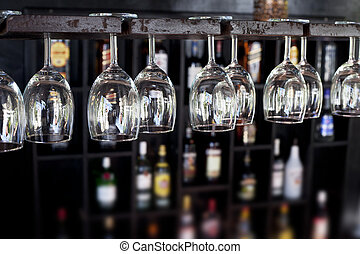 Wine glasses in a bar - Wine glasses hanging upside down in...