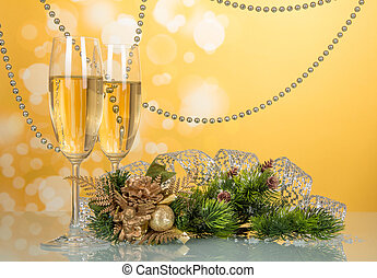 Wine glasses, pine branch, decorated with beads and ribbon, Christmas souvenir on yellow background