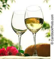 Two wineglasses with white wine on the table outside