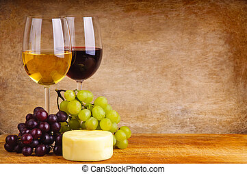 still life composition with glass of red and white wine, cheese and grapes on a wooden background