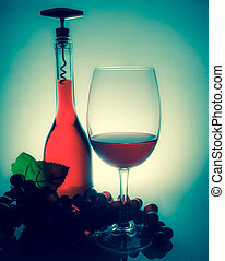 Wine in a glass next to a bottle of wine and grapes on a table with reflection on a vintage wall background