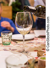 Wine in a glass on a table in a restaurant at a family holiday dinner