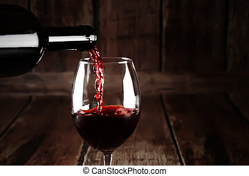 Red wine pour from bottle - Wine in glass on brown wooden...