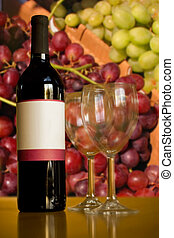 A still life shot of a single wine bottle and a pair of empty glasses in front of some red and green grapes. Shallow depth of field.