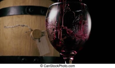 Wine is poured into a glass on the background of a barrel. Slow motion