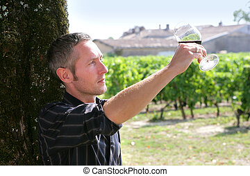 wine maker tasting the wine from his property