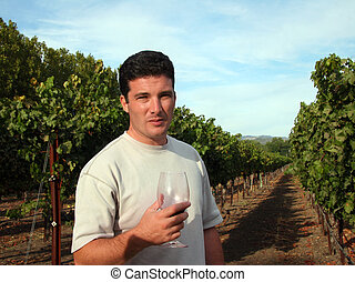 Wine maker - Young man standing at vineyard
