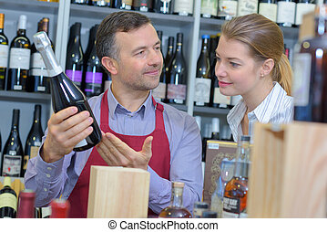 Wine merchant advising customer