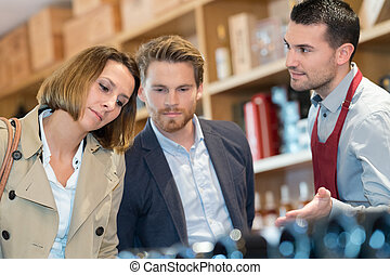 wine merchant making suggestion to young couple