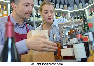 Wine merchant showing presentation packs to customer