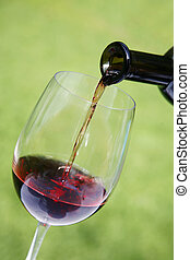 Wine Pouring - Red wine pouring into glass with nice green...