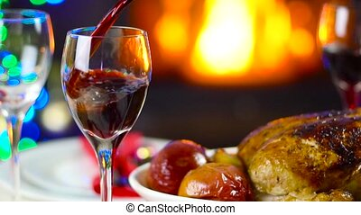wine pouring to glass on christmas table in front of fireplace