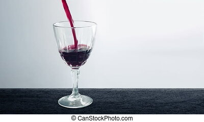 Wine Pours Into Glass On Counter Top - Someone pours red...