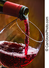 Wine pours into the glass of the bottle on a colored...
