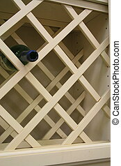 Wooden wine rack with a single bottle.