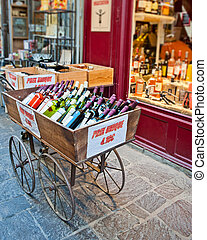 A cart of wine for sale in front of a wine and liquor shop in Uzes France