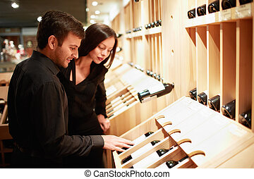 Young couple choosing wine in a store