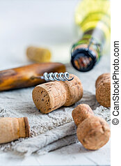 Wine stoppers, old corkscrew and a bottle of wine.