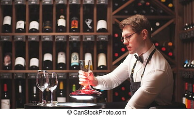 Wine taster or degustator pouring red wine into carafe to...