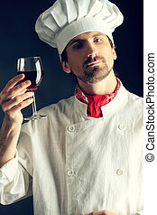 wine tasting - Portrait of a man cook holding a glass of red...