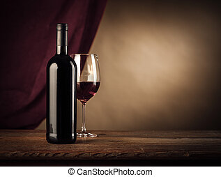 Wine tasting - Red wine bottle and glass on a rustic wooden...