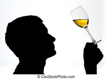 A man in silhouette tasting wine