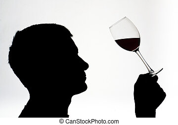 A man in silhouette testing red wine