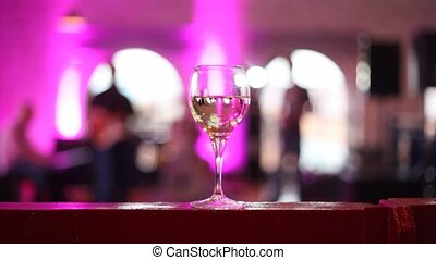 Wineglass stands on table filled with some alcohol in some...