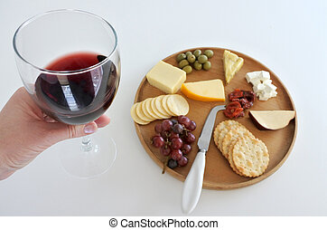 Wineglass with red wine over a cheese platter