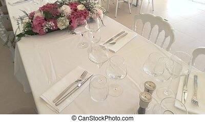 Wineglasses and cutlery on table. Pink and white flowers....