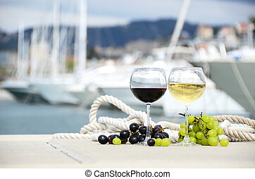 Wineglasses and grapes on the yacht pier of La Spezia, Italy...