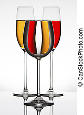 Wineglasses on a shiny surface with different colour fluids that distort reflection