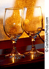 Wineglasses - Two empty wine glasses reflecting sunlight on...