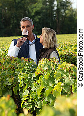 Winegrowers in the vineyard with a glass of wine