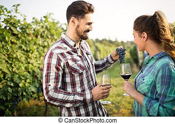 Winegrowers tasting wine in vineyard