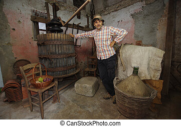 winemaker at the grapes press - winemaker next to old press ...