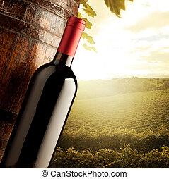 Wine bottle and wodden barrel with sunny rural landscape on background.