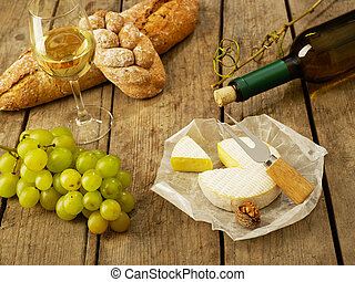 Winetasting - Bread, grapes, wine and cheese on cutting...