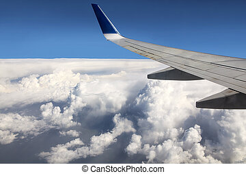 Wing aircraft over cumulus clouds.
