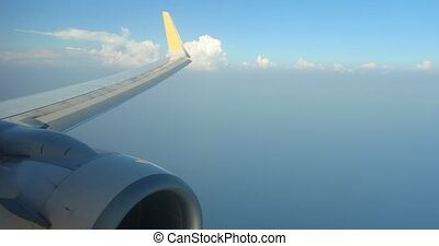 Wing flaps Adjust above cloud bank on commercial airliner. ...