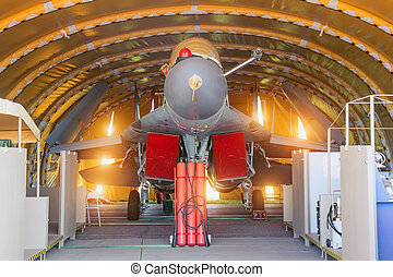 Wing military fighter with folded wings in the garage of the hangar on service repair.