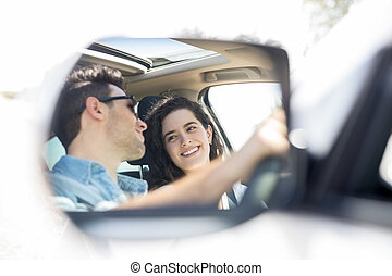 Wing mirror reflection of happy couple driving car